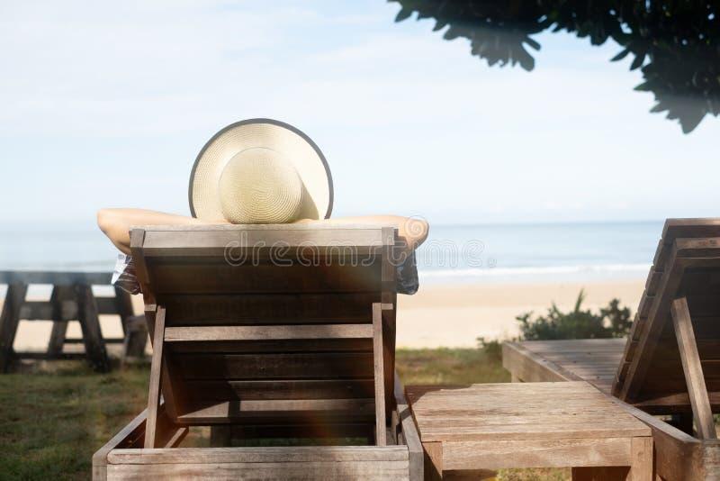 Jeune femme de vacances de plage d'été avec le chapeau détendant sur le nea de chaise photographie stock