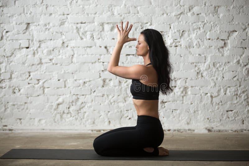 Jeune femme de yogi dans la pose de vajrasana avec le namaste, fond de grenier photos libres de droits