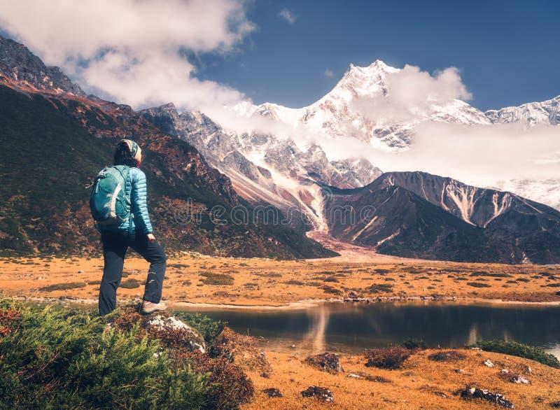 Jeune femme debout avec le sac à dos et les montagnes images stock