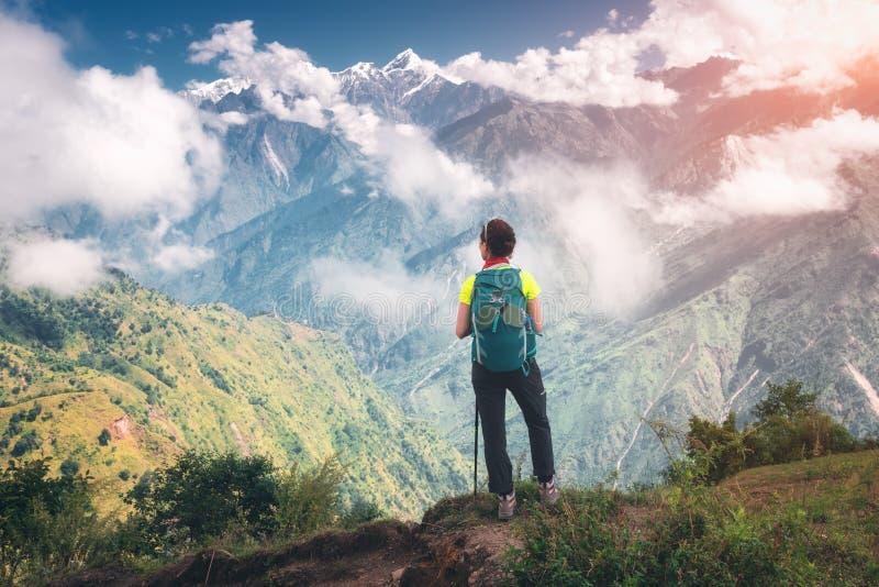 Jeune femme debout avec le sac à dos sur la crête de montagne photos stock