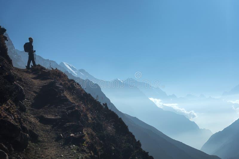 Jeune femme debout sur la colline et regard sur des montagnes photo libre de droits