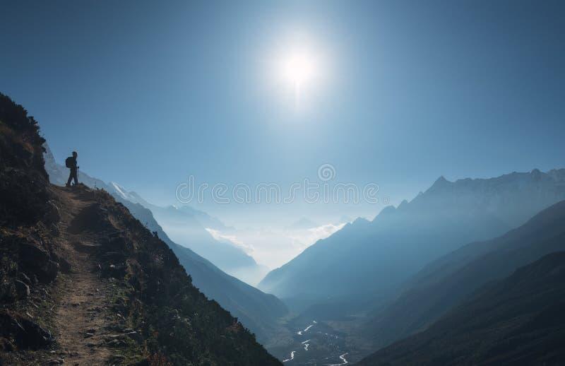 Jeune femme debout sur la colline et regard sur des montagnes image libre de droits
