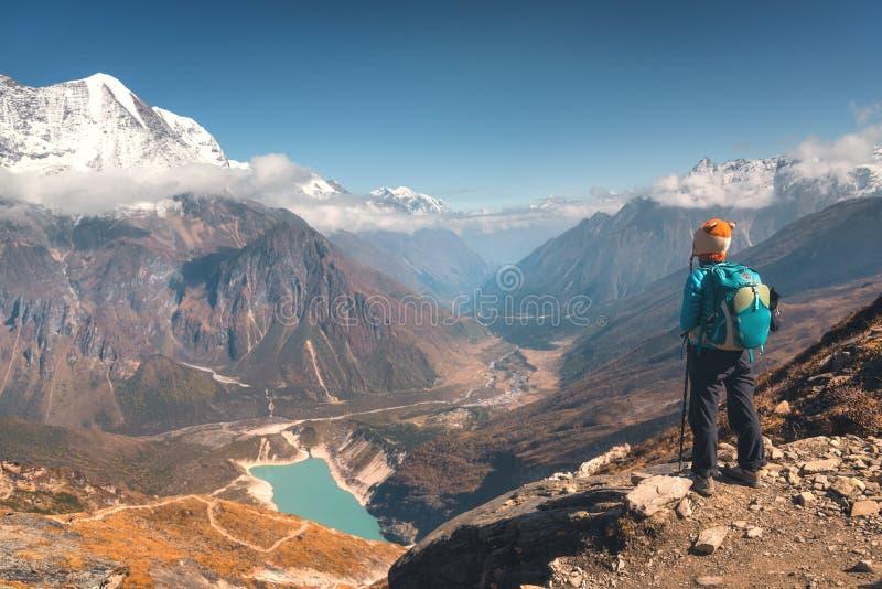 Jeune femme debout sur la crête de montagne contre le lac photographie stock