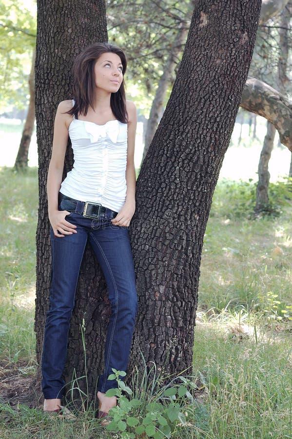 Jeune femme dernier cri par des arbres photos stock