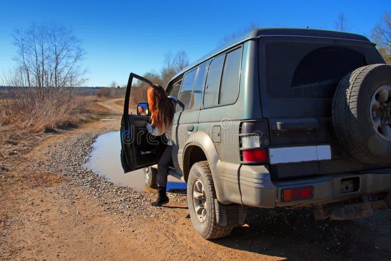 Jeune femme derrière le gouvernail de direction du véhicule tous terrains sur la saleté r images stock