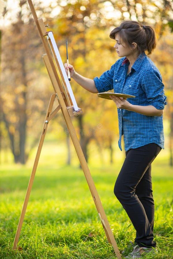 Jeune femme dessinant une image sur la toile sur un chevalet dans la nature, la fille de peintre détendant, un concept de mode de photo libre de droits