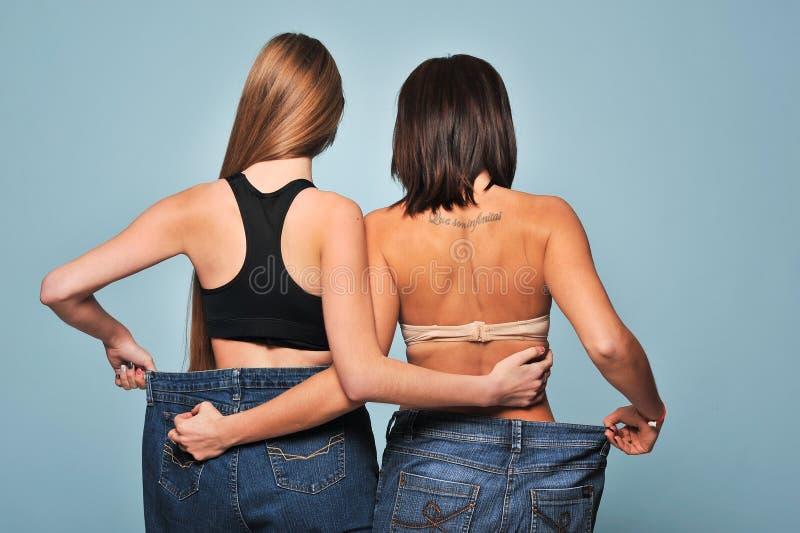 Jeune femme deux convenable dans des jeans lâches photographie stock libre de droits