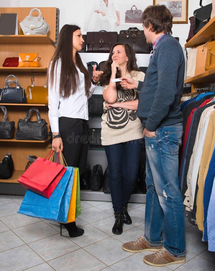 Jeune femme deux heureuse avec des paniers et des ventes masculines assistan photographie stock