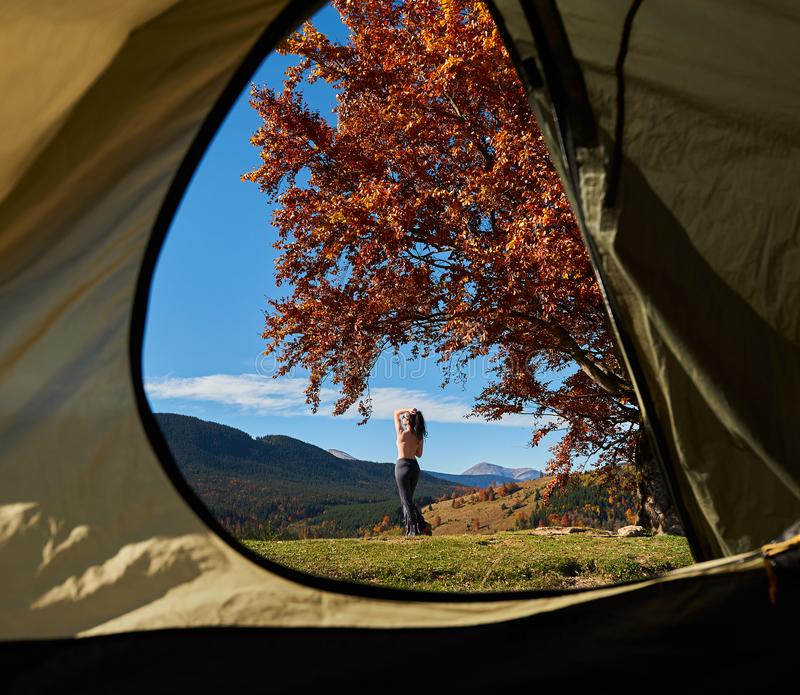 Jeune femme devant la tente de touristes, vue de l'intérieur, sur le fond des collines boisées et du ciel bleu photo stock