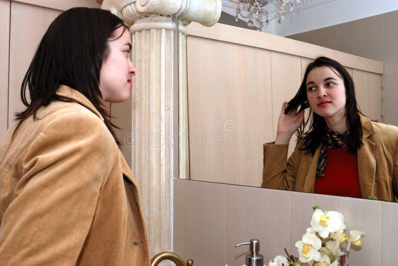 Jeune femme devant un miroir photo stock