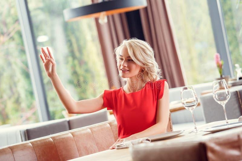 Jeune femme dinant dans le restaurant se reposant saluant le serveur gai photo stock