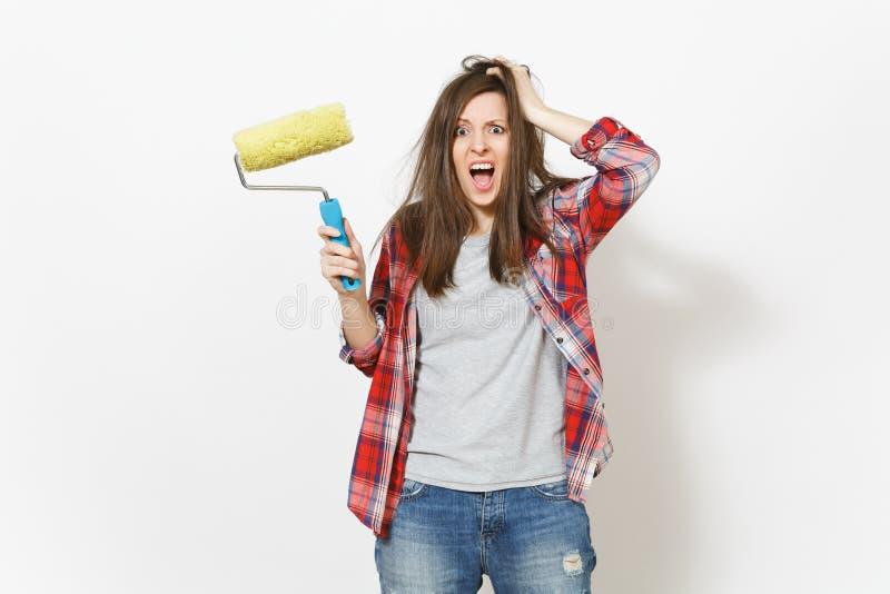 Jeune femme dingue folle dans des vêtements sport tenant le rouleau de peinture pour la peinture de mur et s'accrochant pour se d photos libres de droits