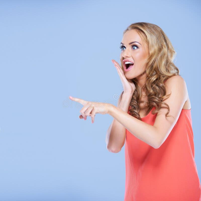 Jeune femme dirigeant son doigt à quelque chose images libres de droits