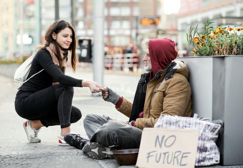 Jeune femme donnant l'argent à l'homme sans abri de mendiant s'asseyant dans la ville photo libre de droits