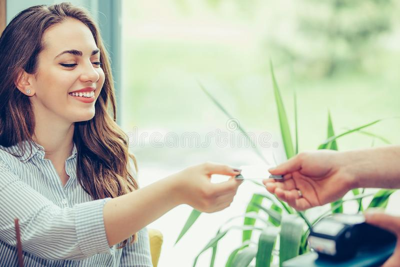 Jeune femme donnant la carte de crédit à la main de serveur et payant le café au café photographie stock libre de droits