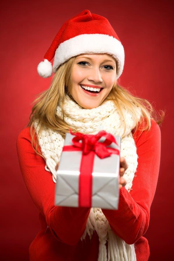 Jeune femme donnant le cadeau de Noël photographie stock libre de droits