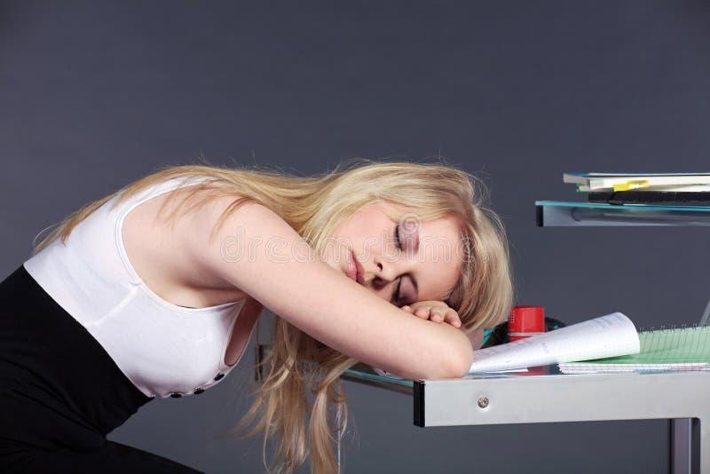 Jeune femme dormant au-dessus du schoolwork photo stock