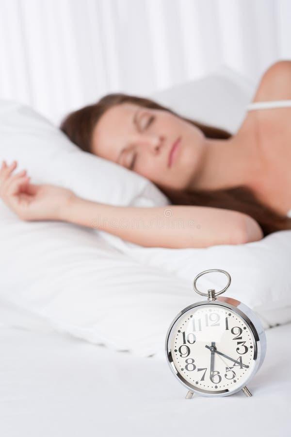 Jeune Femme Dormant Dans Le Bâti Avec L Horloge D Alarme Photo libre de droits