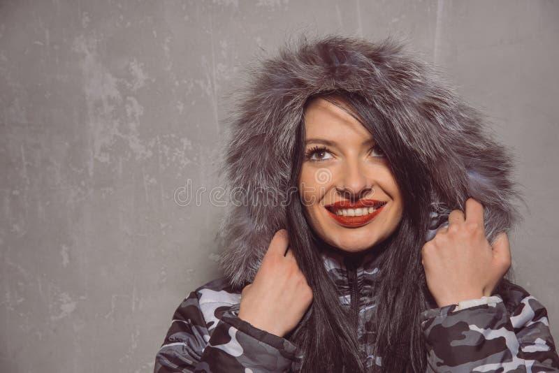 Jeune femme douce dans la veste chaude d'hiver avec le capot de fourrure photographie stock libre de droits
