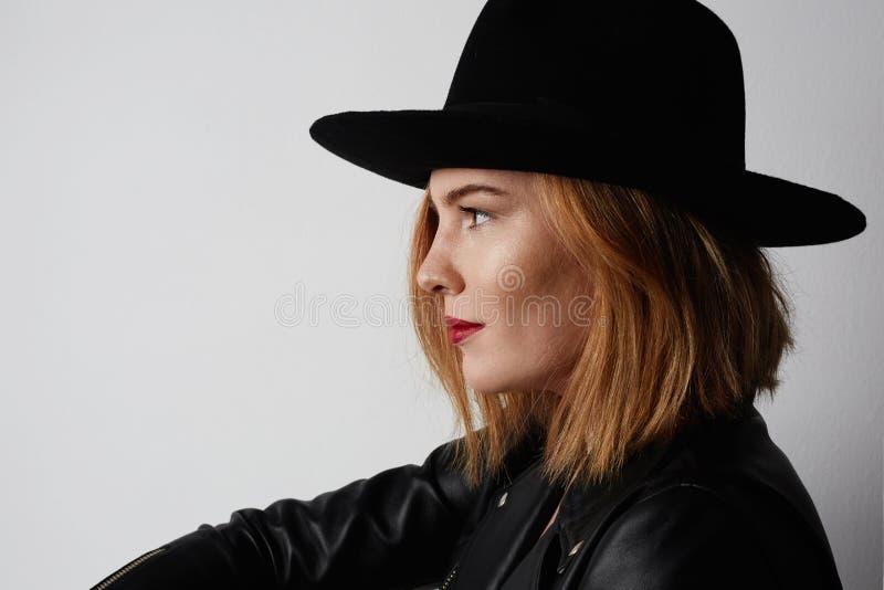 Jeune femme douce de portrait de mode jolie dans les vêtements élégants et le chapeau noir posant sur le fond blanc image libre de droits