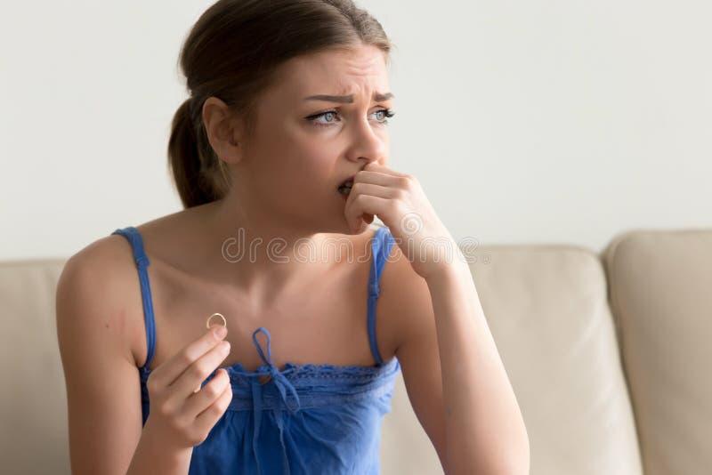 Jeune femme douteuse tenant l'anneau de mariage, hésitant au sujet du marr images stock