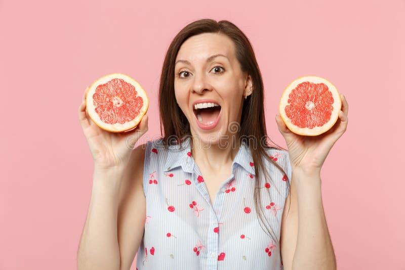 Jeune femme drôle étonnée maintenant la bouche grande ouverte tenant deux halfs de pamplemousse mûr frais d'isolement sur le past photos stock