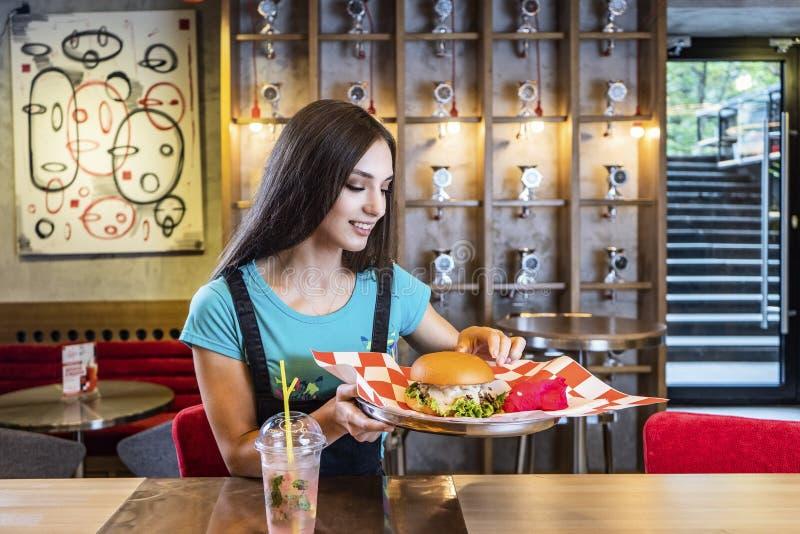 Jeune femme drôle blonde mangeant un hamburger au CAM extérieur image stock