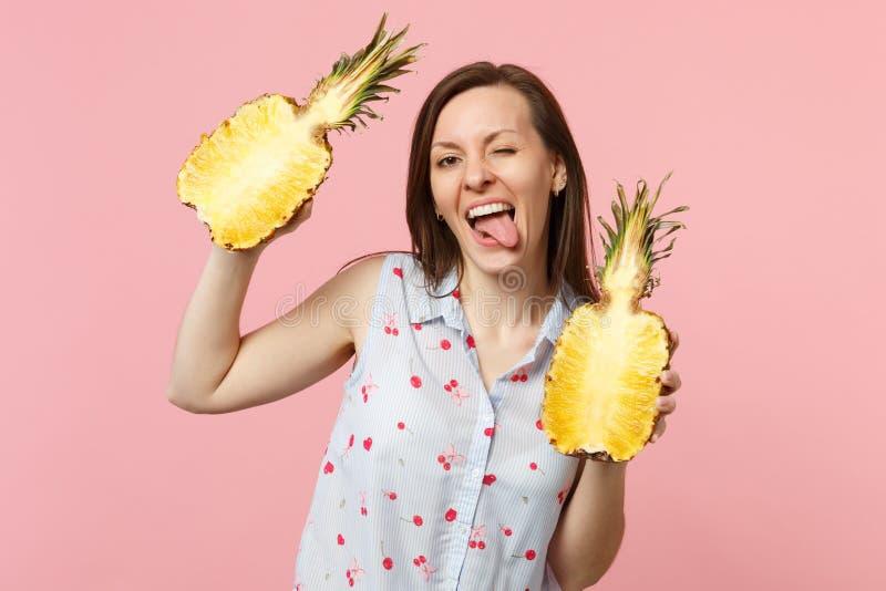 Jeune femme drôle dans des vêtements d'été montrant la langue tenant des halfs du fruit mûr frais d'ananas d'isolement sur le pas photographie stock libre de droits