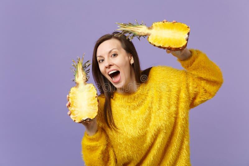 Jeune femme drôle dans le chandail de fourrure gardant les halfs se tenants ouverts de bouche du fruit mûr frais d'ananas d'isole images libres de droits