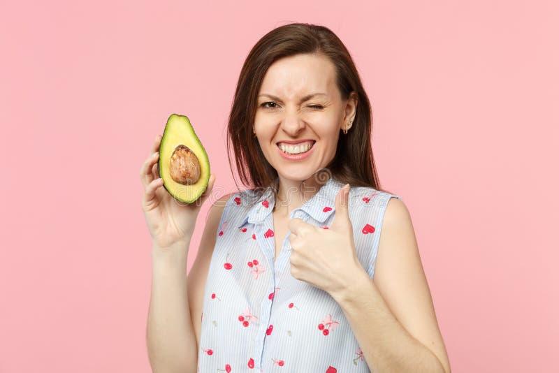 Jeune femme drôle de clignotement dans des vêtements d'été montrant le pouce vers le haut de l'avocat vert mûr frais de prise d'i images stock