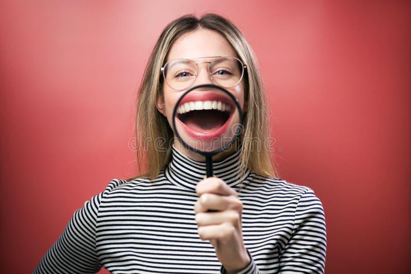 Jeune femme drôle montrant sa loupe de trought de bouche au-dessus de fond rose images libres de droits
