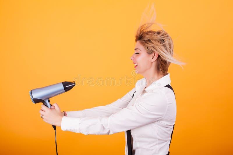 Jeune femme drôle soufflant ses cheveux courts avec un drayer de cheveux au-dessus de fond jaune photographie stock