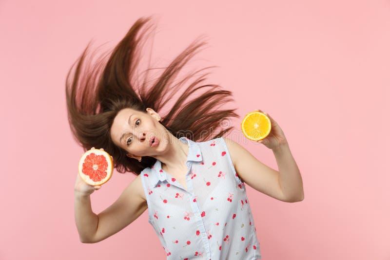 Jeune femme drôle stupéfaite avec les cheveux de flottement tenant des halfs du fruit orange de pamplemousse mûr frais d'isolemen photo stock