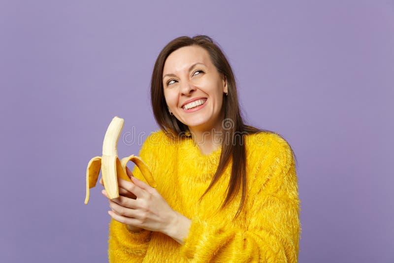 Jeune femme dreamful joyeuse dans le chandail de fourrure recherchant, jugeant à disposition le fruit mûr frais de banane d'isole image libre de droits