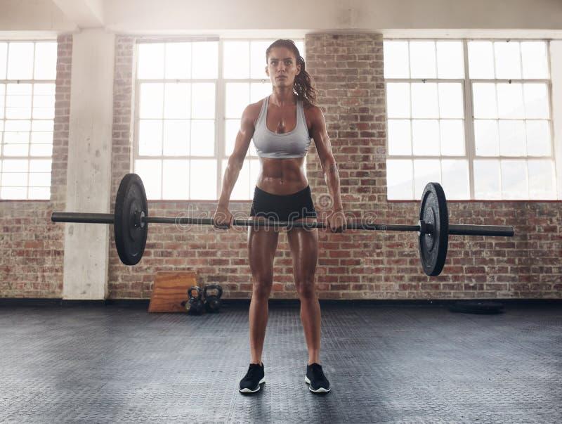 Jeune femme dure s'exerçant avec le barbell photos stock