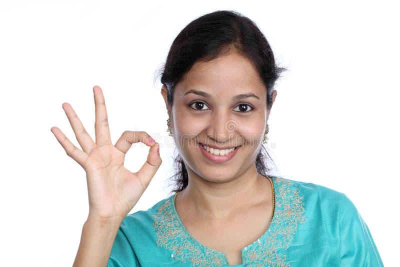 Jeune femme effectuant le signe EN BON ÉTAT photographie stock