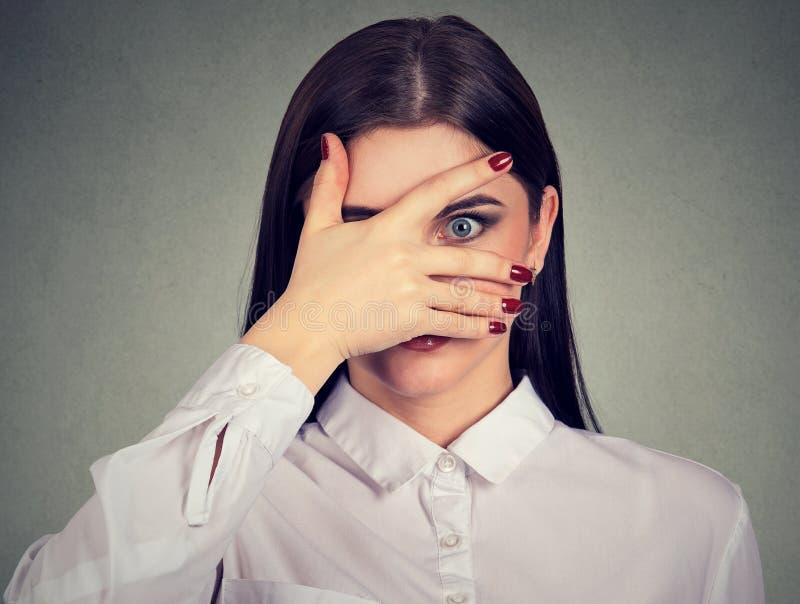 Jeune femme effrayée jetant un coup d'oeil par ses doigts photos stock
