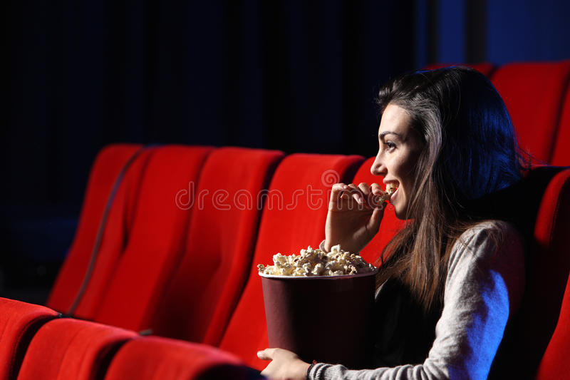 Jeune femme, elle mange du maïs éclaté et sourit image libre de droits