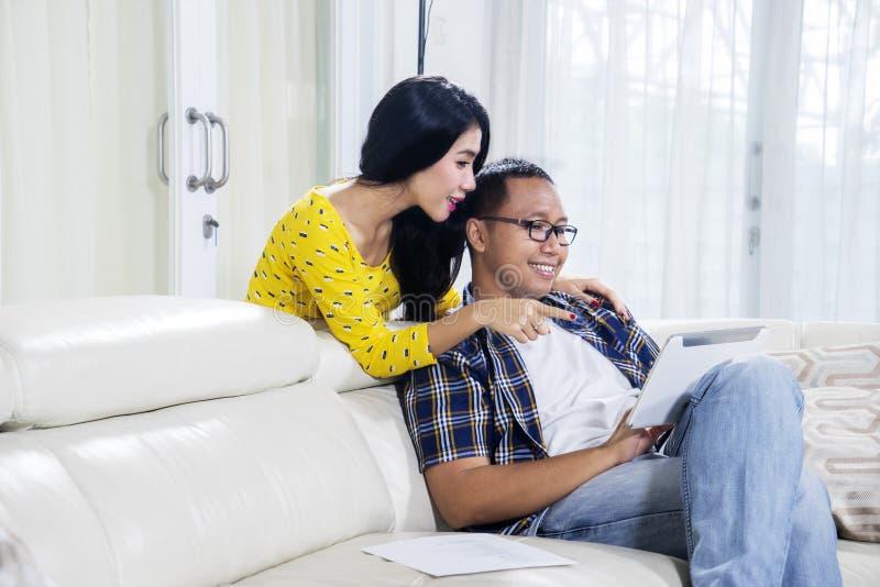 Jeune femme embrassant son mari à la maison image stock