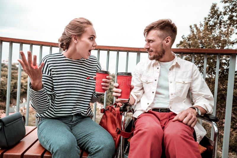 Jeune femme employant des gestes tout en parlant à son ami attentif image stock