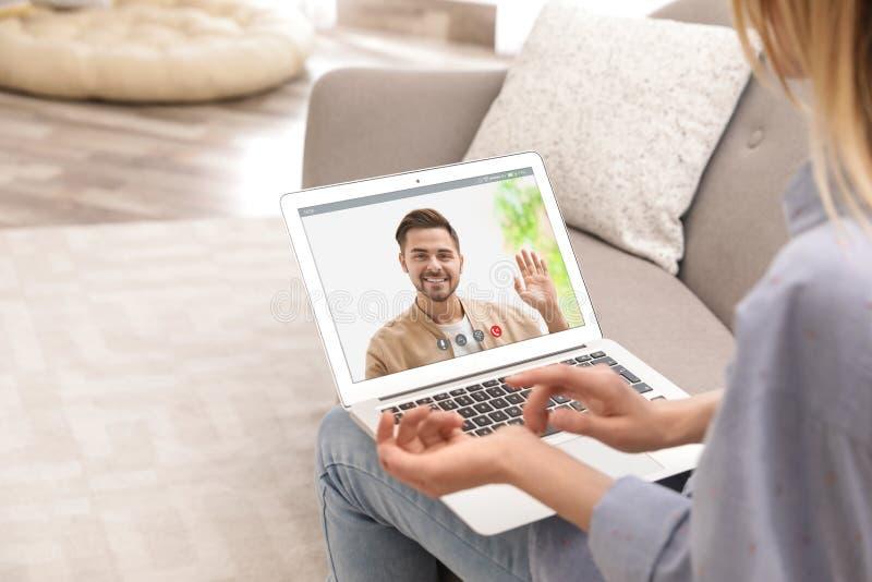 Jeune femme employant la causerie visuelle sur l'ordinateur portable dans le salon photo libre de droits