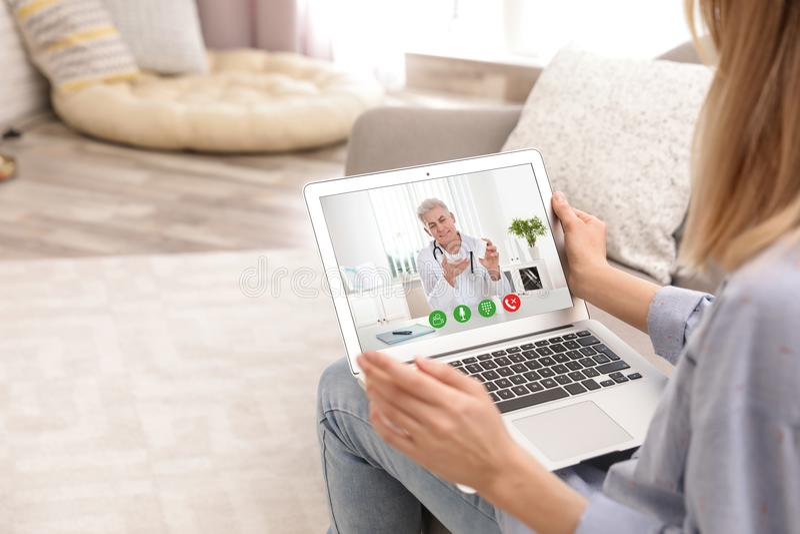 Jeune femme employant la causerie visuelle sur l'ordinateur portable dans le salon photographie stock