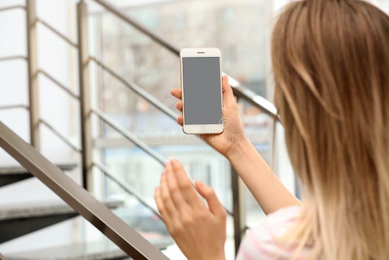 Jeune femme employant la causerie visuelle sur le smartphone ? l'int?rieur photographie stock