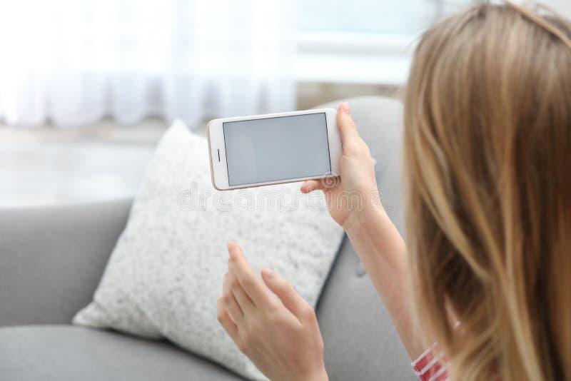 Jeune femme employant la causerie visuelle sur le smartphone dans le salon L'espace pour la conception photos libres de droits