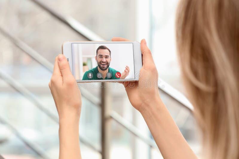 Jeune femme employant la causerie visuelle sur le smartphone ? l'int?rieur images stock