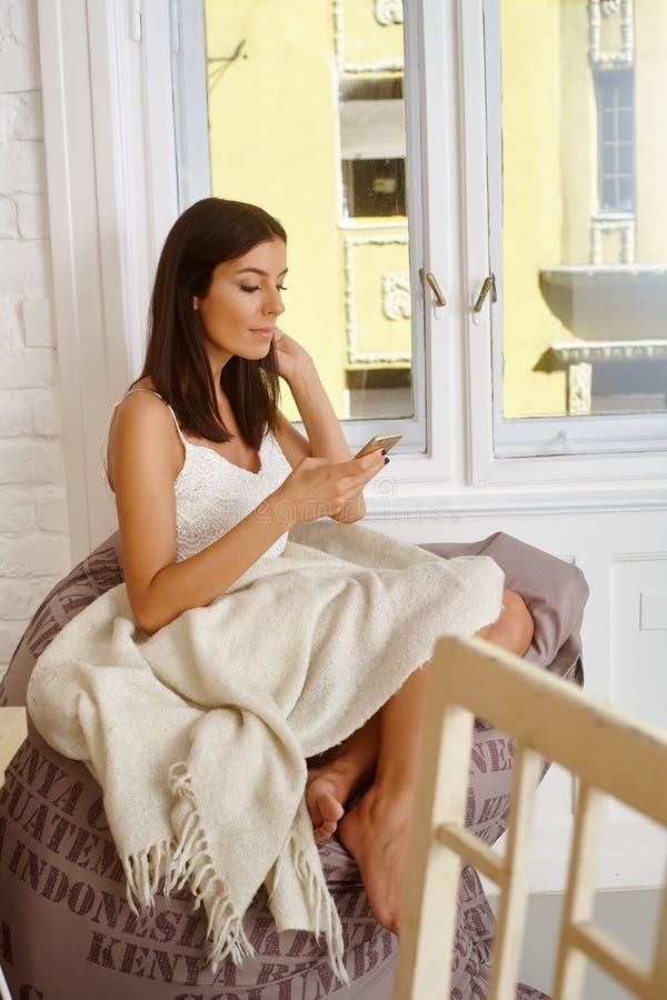Jeune femme employant le mobile à la maison image stock