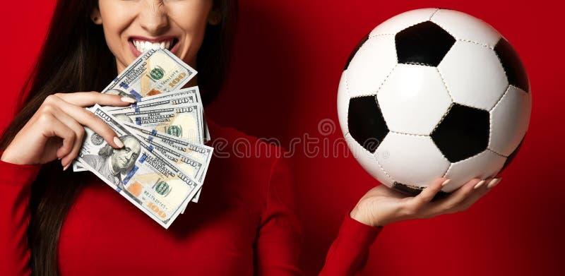 Jeune femme en ballon de football de prise et argent uniformes rouges du dollar pour des sports pariant la c?l?bration photo libre de droits