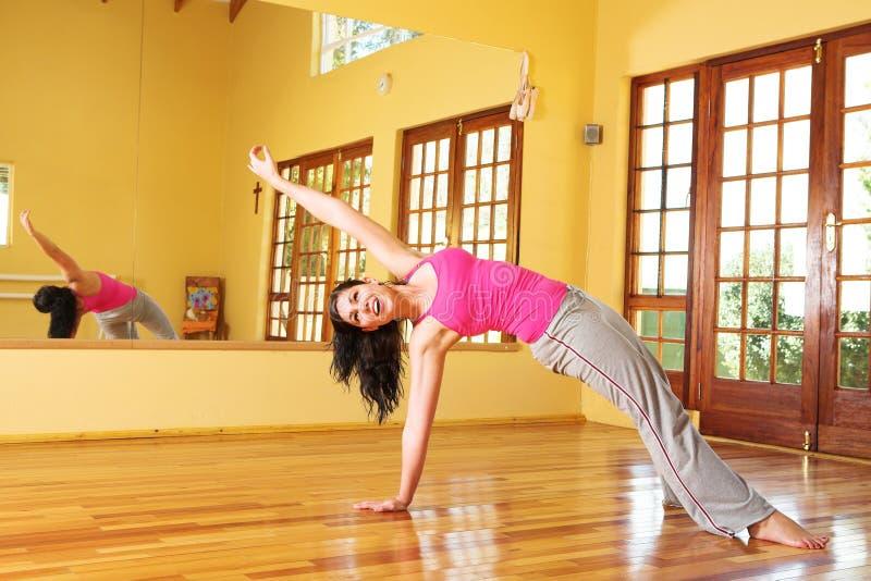 Jeune femme en bonne santé dans l'étirage d'équipement de gymnastique image stock