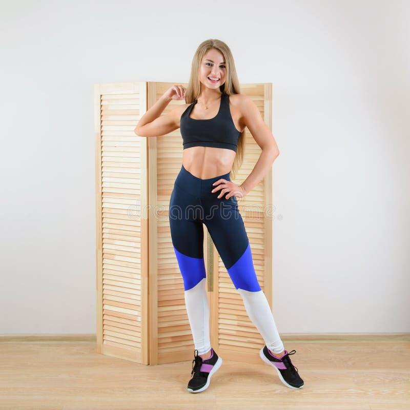 Jeune femme en bonne santé dans la pose de vêtements de sport Belle fille heureuse souriant à l'appareil-photo photographie stock