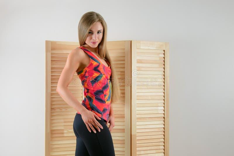 Jeune femme en bonne santé dans la pose de vêtements de sport Belle fille heureuse souriant à l'appareil-photo photos stock